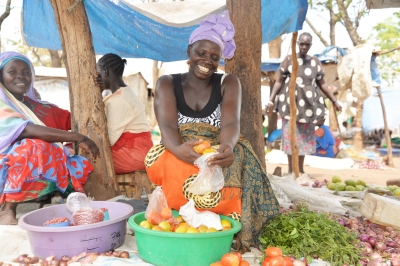 Woman sorting tomatoes for her customer at the marketplace. Photo credit: VisionFund International 2019.